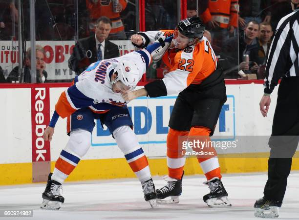 Dale Weise of the Philadelphia Flyers fights Travis Hamonic of the New York Islanders in the first period on March 30 2017 at the Wells Fargo Center...