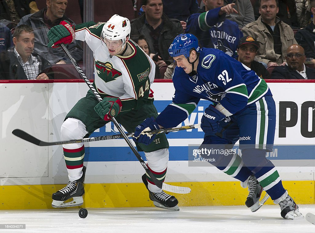 Dale Weise #32 of the Vancouver Canucks and Justin Falk #44 of the Minnesota Wild compete for the puck during their NHL game at Rogers Arena March 18, 2013 in Vancouver, British Columbia, Canada. Minnesota won 3-1.