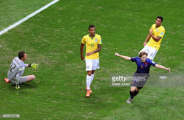 Daley Blind of the Netherlands celebrates scoring his team's second goal as goalkeeper Julio Cesar Luiz Gustavo and Paulinho of Brazil react during...