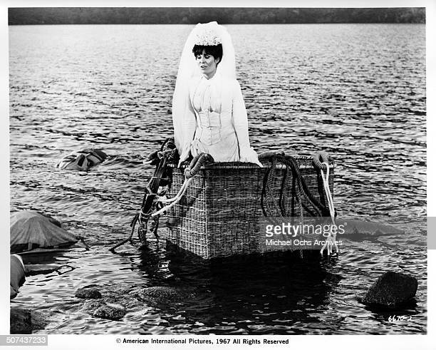 Daliah Lavi as Madelaine stands in a balloon basket as it floats in a lake in a scene from the movie 'Those Fantastic Flying Fools' circa 1967