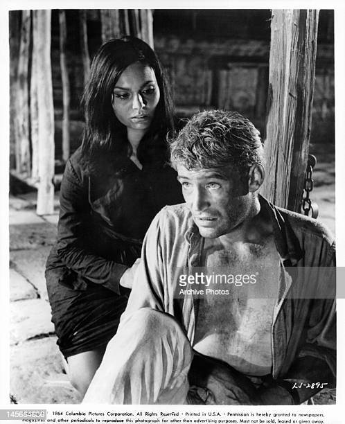 Daliah Lavi goes to Peter O'Toole's aid as he slumps against the stake in chains in a scene from the film 'Lord Jim' 1965