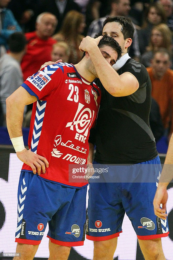 Dalibor Cutura of Serbia (R) comforts Nenad Vuckovic of Serbia (L) during the Men's European Handball Championship final match between Serbia and Denmark at Beogradska Arena on January 29, 2012 in Belgrade, Serbia.