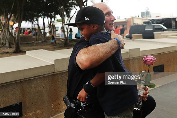 Dallas Assistant Chief of Police Gary Tittle recieves a hug from Jacob Flanagan at a growing memorial at the Dallas poice department's headquarters...