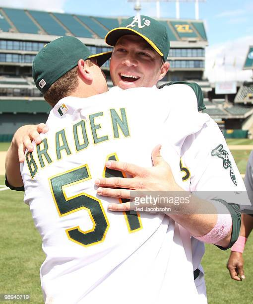 Dallas Braden of the Oakland Athletics celebrates with his catcher Landon Powell after pitching a perfect game against the Tampa Bay Rays during an...