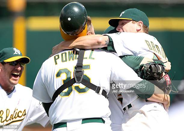 Dallas Braden of the Oakland Athletics celebrates with his catcher Landon Powell and Adam Rosales after pitching a perfect game against the Tampa Bay...