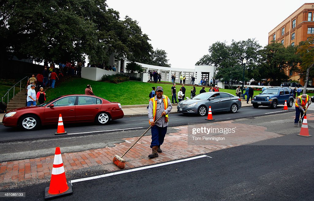 Dallas city workers repair the asphalt on Elm Street in Dealey Plaza as people visit Dealey Plaza on November 21, 2013 in Dallas, Texas. People visited the John F. Kennedy Memorial Plaza and Dealey Plaza on the eve of the 50th anniversary of the assassination of U.S. President John F. Kennedy as he rode in a Presidential motorcade in Dealey Plaza.