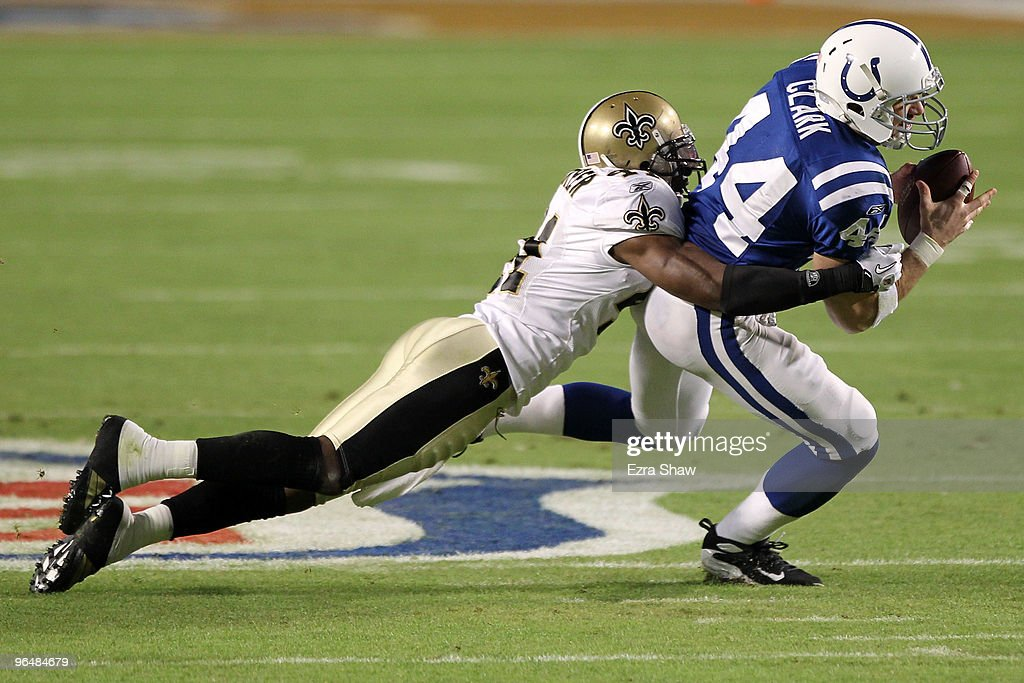 Dallas Clark of the Indianapolis Colts runs with the ball after making a catch against Roman Harper of the New Orleans Saints during Super Bowl XLIV...