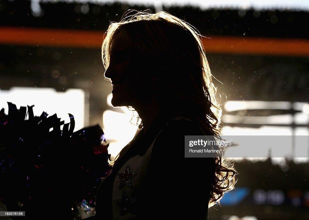A Dallas Cowboys Cheerleader performs at AT&T Stadium on October 6, 2013 in Arlington, Texas.