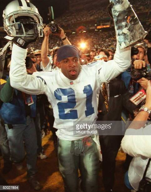 Dallas Cowboys cornerback Deion Sanders hoists the Vince Lombardi Super Bowl trophy as he walks off the field to the locker room after defeating the...
