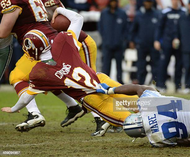 Dallas Cowboys defensive end DeMarcus Ware hangs onto Washington Redskins quarterback Kirk Cousins after making a third down stop in the fourth...
