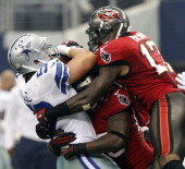Dallas Cowboys inside linebacker Sean Lee pulls down an interception as he is hit by Tampa Bay Buccaneers DJ Ware and Arrelious Benn as the Dallas...