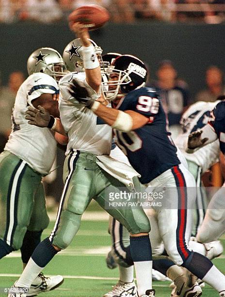 Dallas Cowboys' quarterback Jason Garrett is hit by the New York Giants' Corey Widmer just as he releases the ball in the first quarter 21 September...