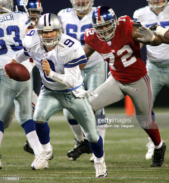 Dallas Cowboys quarterback Tony Romo scrambles past New York Giants defensive end Osi Umenyiora during fourth quarter action The Cowboys defeated the...