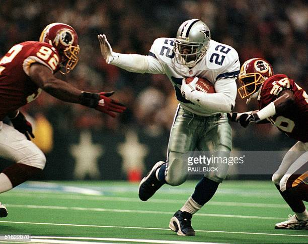 Dallas Cowboys running back Emmitt Smith rushes his way to a short gain as Washington Redskin defenders Jamal Duff and Chris Dishman close in during...
