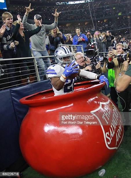 Dallas Cowboys running back Ezekiel Elliott jumps into the Salvation Army red kettle after scoring a second quarter touchdown against the Tampa Bay...