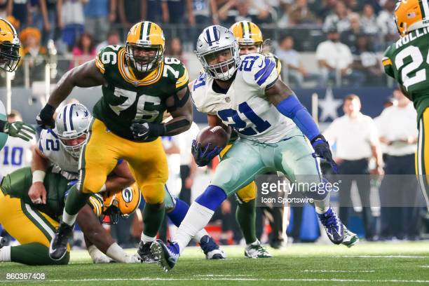 Dallas Cowboys running back Ezekiel Elliott runs through a gap in the line during the football game between the Green Bay Packers and Dallas Cowboys...