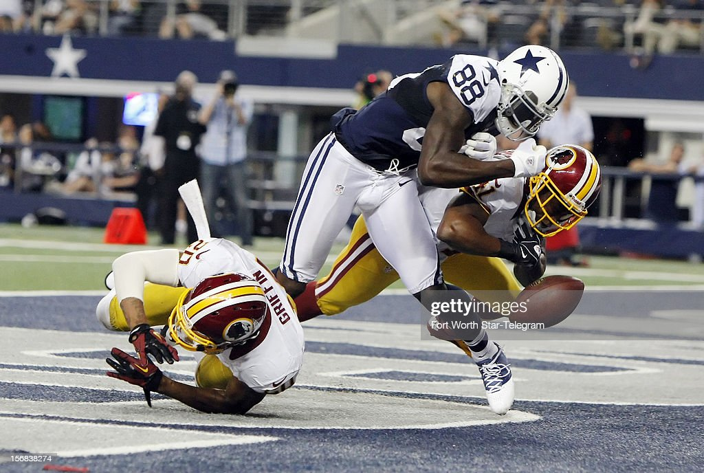Dallas Cowboys wide receiver Dez Bryant (88) is unable to hold onto the ball for a touchdown as Washington Redskins free safety Madieu Williams (41) and defensive back Cedric Griffin (20) defend during the second half at Cowboys Stadium in Arlington, Texas, Thursday, November 22, 2012. The Redskins defeated the Cowboys, 38-31.