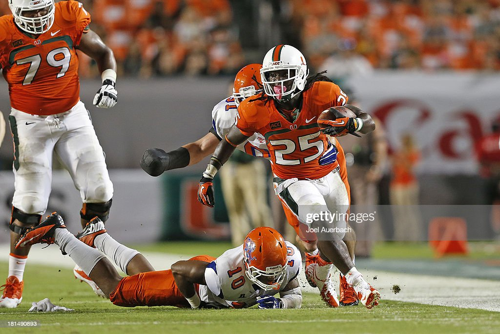 Dallas Crawford #25 of the Miami Hurricanes runs with the ball past Justin Dixon #10 of the Savannah State Tigers on September 21, 2013 at Sun Life Stadium in Miami Gardens, Florida.