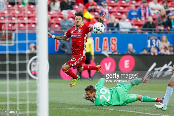 Dallas forward Maximiliano Urruti appears to score a goal over Sporting Kansas City goalkeeper Tim Melia but is called offsides during the MLS match...