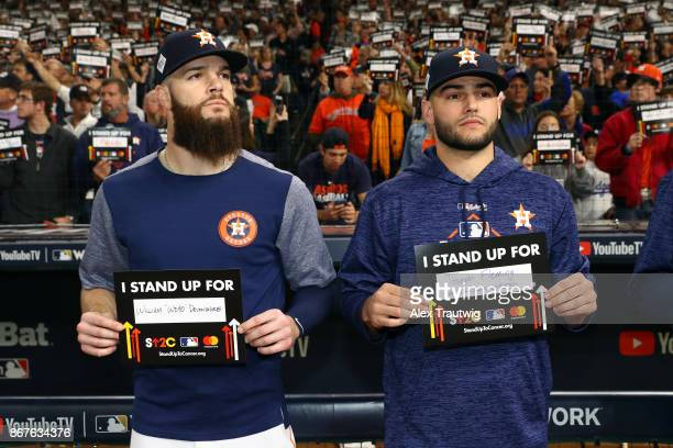 Dallas Keuchel and Lance McCullers Jr #43 of the Houston Astros stand outside the dugout holding Stand Up 2 Cancer placards during Game 4 of the 2017...