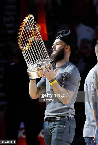 Dallas Keuchel of the Houston Astros holds the World Series Trophy during a timeout in the first half during the game between the Houston Rockets and...