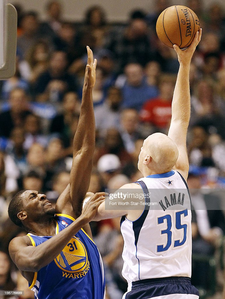 Dallas Mavericks center Chris Kaman (35) attempts a shot as Golden State Warriors center Festus Ezeli (31) defends during the first half of an NBA basketball game at the American Airlines Center in Dallas, Texas, Monday, November 19, 2012.