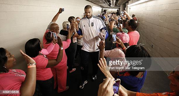 Dallas Mavericks center Tyson Chandler runs highfives his way through cheering breast cancer survivors forming a double line en route to the court as...
