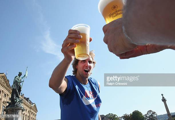 Dallas Mavericks forward Dirk Nowitzki holds a glass of beer while he arrives at the Wuerzburg Residence on June 28 2011 in Wuerzburg Germany...