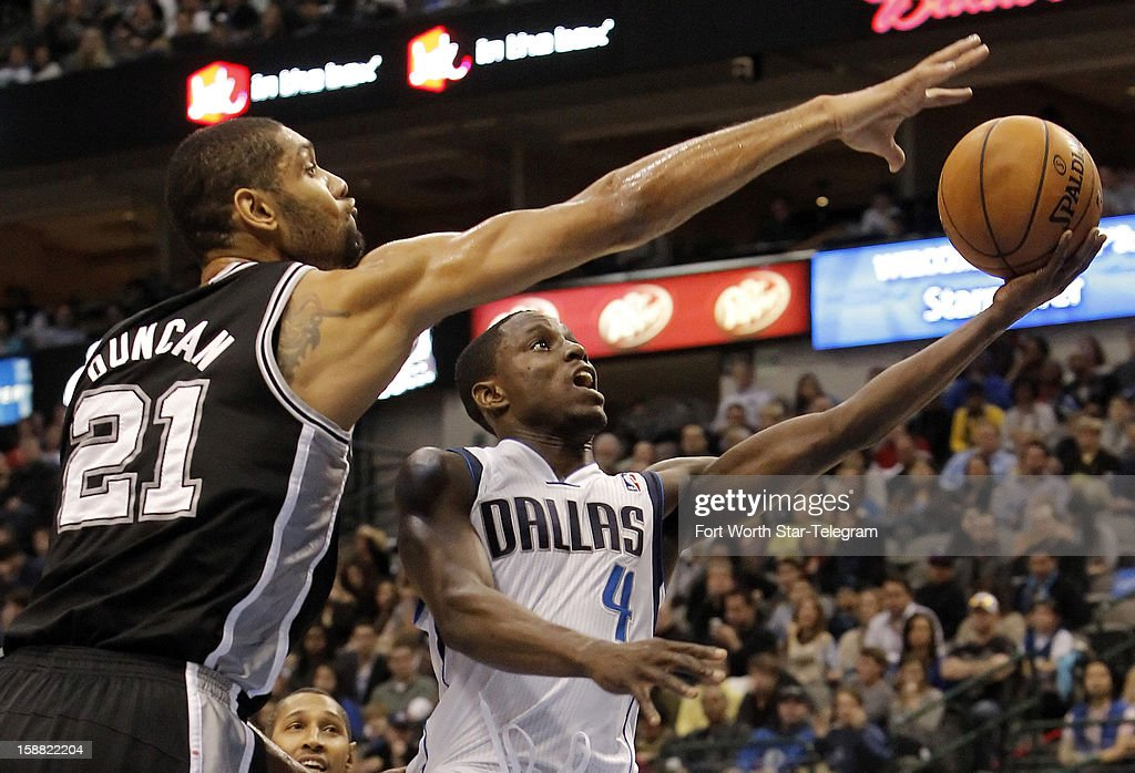 Dallas Mavericks guard Darren Collison (4) attempts a layup as San Antonio Spurs forward Tim Duncan (21) defends during the first half of a basketball game at American Airlines Center in Dallas, Texas, Sunday, December 30, 2012.