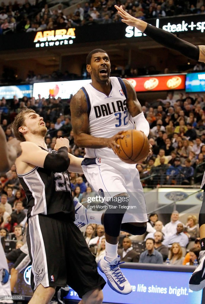 Dallas Mavericks guard O.J. Mayo (32) attempts a shot as San Antonio Spurs center Tiago Splitter (22) defends during the first half of a basketball game at American Airlines Center in Dallas, Texas, Sunday, December 30, 2012.