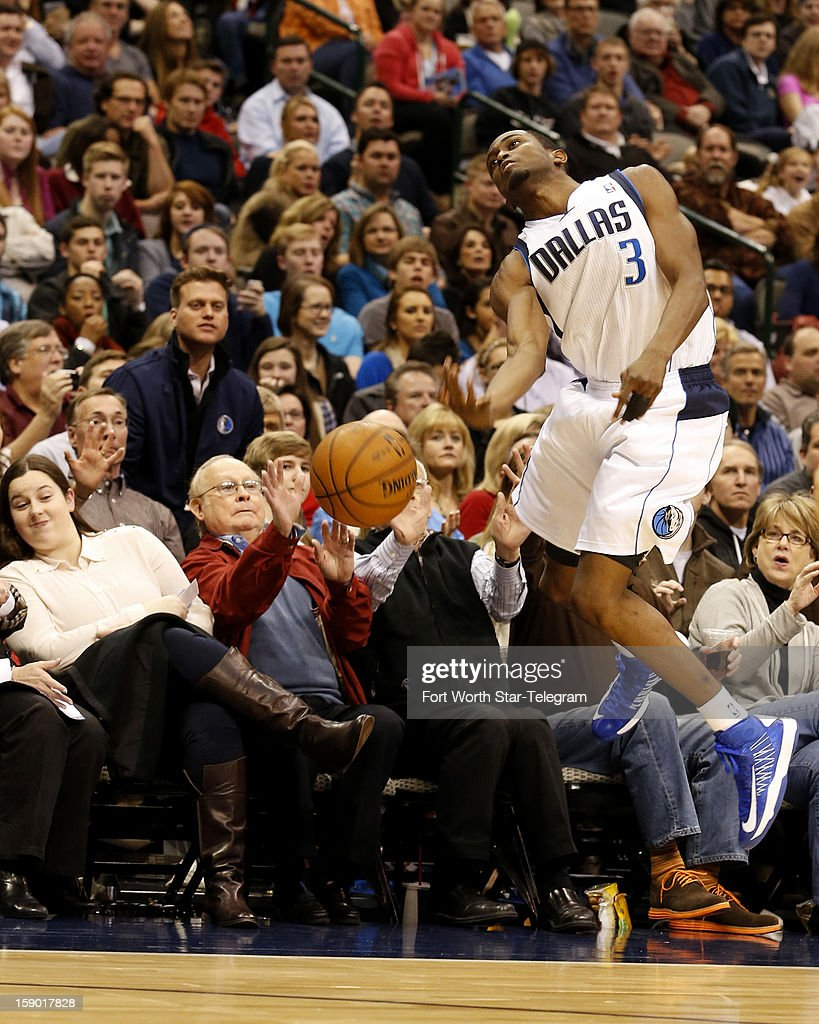 Dallas Mavericks guard Rodrigue Beaubois keeps from crashing into the fans as he keeps the ball inbounds during the second half against the New Orleans Hornets at the American Airlines Center in Dallas, Texas, Saturday, January 5, 2013. The Hornets defeated the Mavericks in overtime, 99-96.