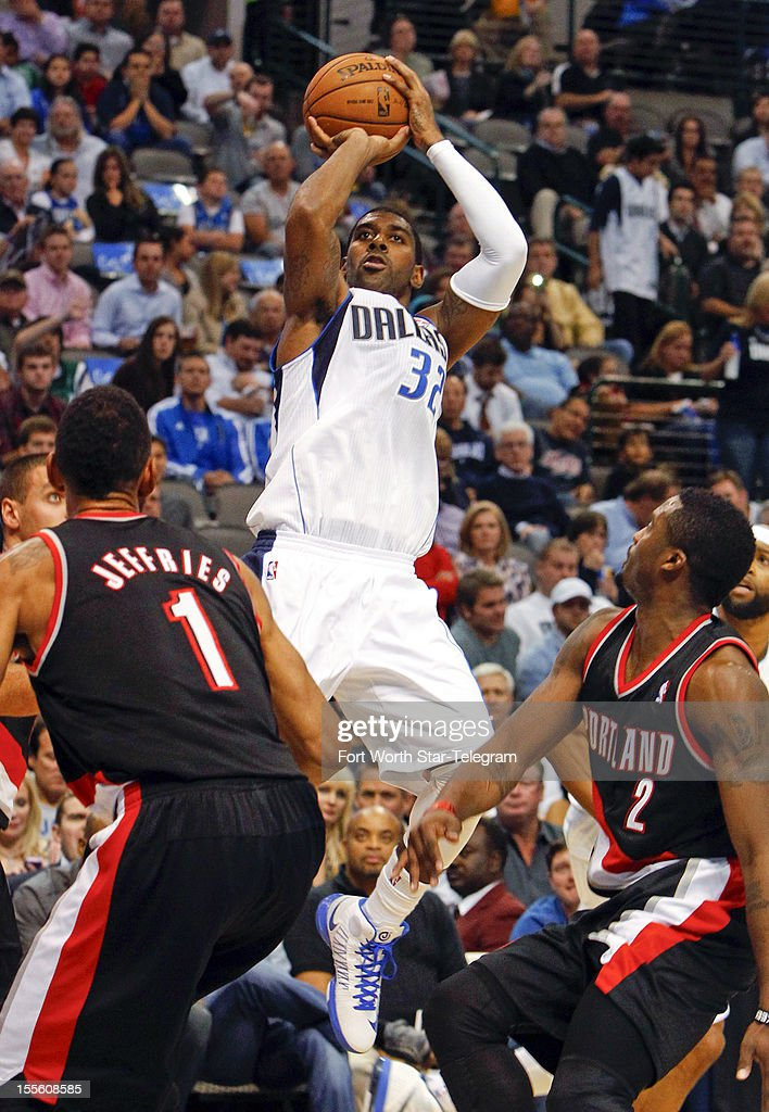 Dallas Mavericks O.J. Mayo (32) puts up a shot over Portland Trail Blazers Jared Jeffries (1) and Wesley Matthews (2) in a basketball game at American Airlines Center Monday, November 5, 2012, in Dallas, Texas.