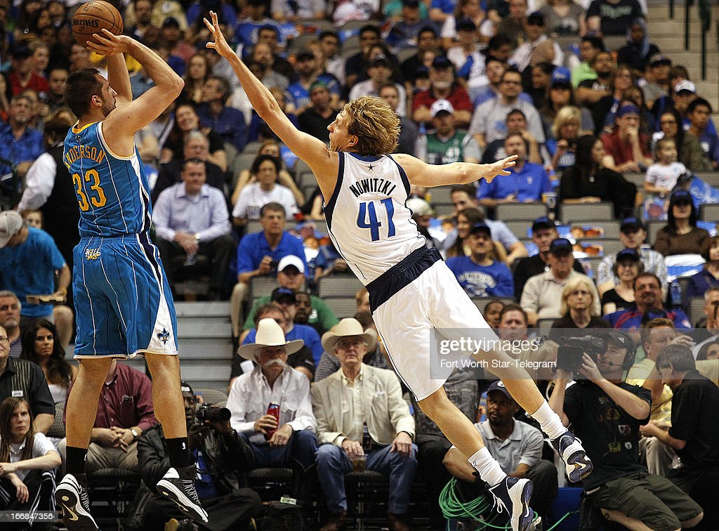 Dallas Mavericks power forward Dirk Nowitzki (41) defends as New Orleans Hornets power forward Ryan Anderson (33) launches a three-point shot on Wednesday April 17, 2013, in Dallas, Texas.
