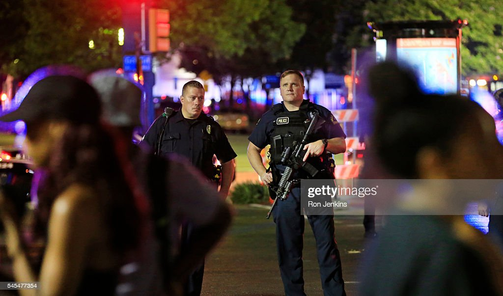 Dallas police and residents stand near the scene where four Dallas police officers were shot and killed on July 7 2016 in Dallas Texas According to...