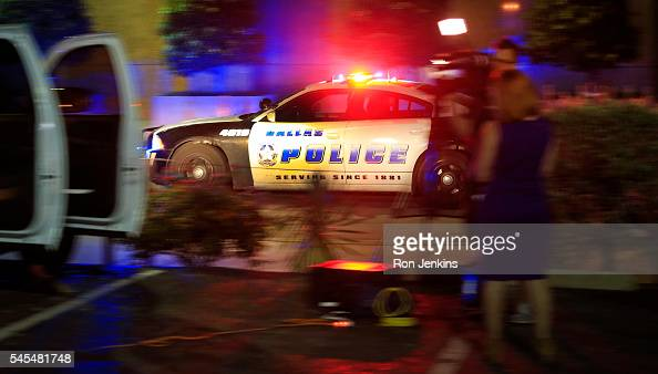 Dallas police officer drives near the scene where eleven Dallas police officers were shot and five have now died on July 8 2016 in Dallas Texas...