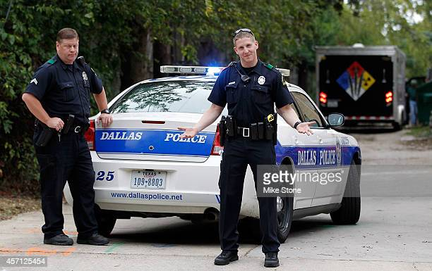 Dallas police officer responds to media questions as hazmat company CG Environmental Cleaning Guys begins setup at the apartment where a second...