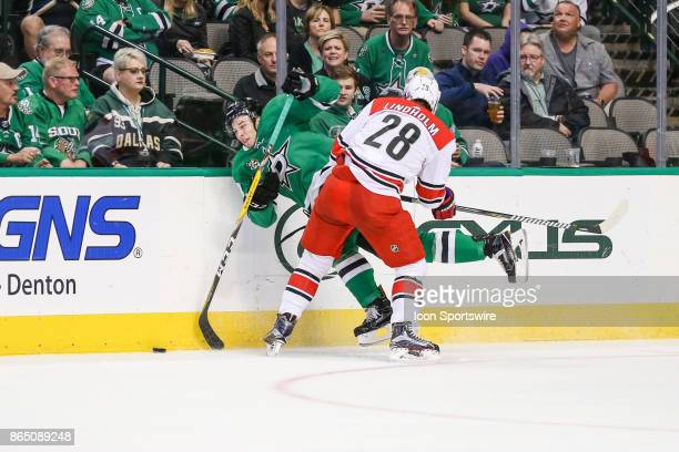 Dallas Stars center Tyler Pitlick gets checked into the boards by Carolina Hurricanes center Elias Lindholm during the game between the Dallas Stars...