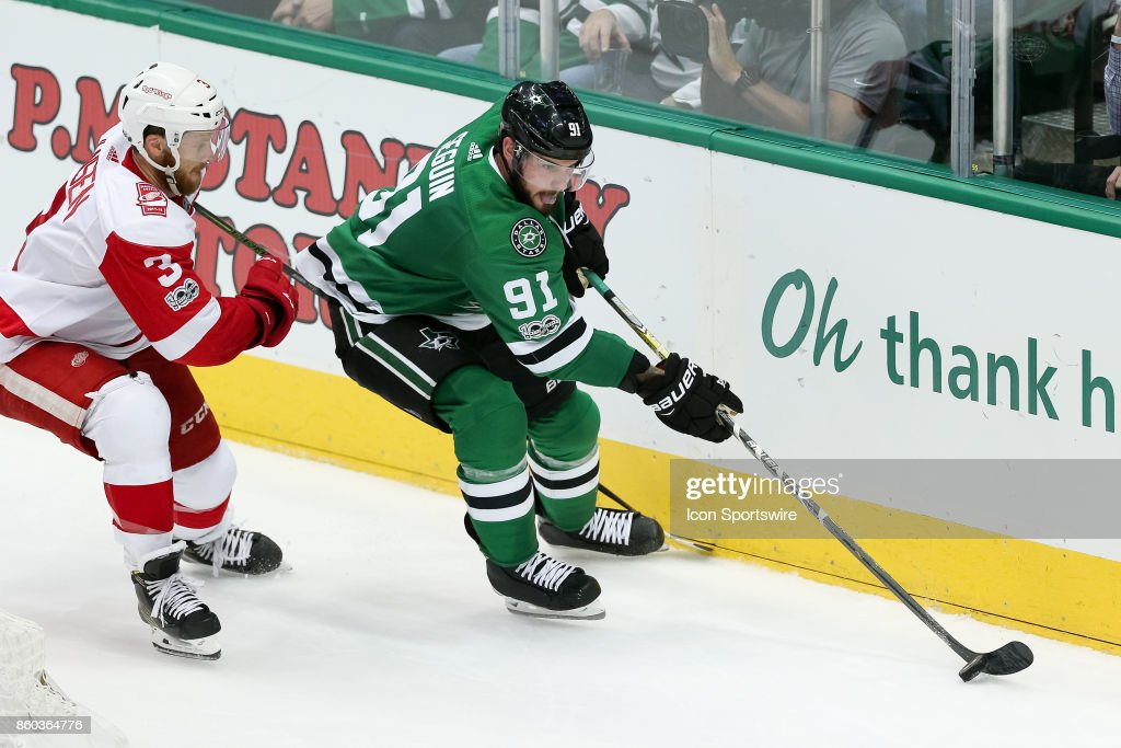 Dallas Stars Center Tyler Seguin (91) takes the puck along the boards while being pursued by Detroit Red Wings Defenceman Nick Jensen (3) during the NHL game between the Detroit Red Wings and Dallas Stars on October 10, 2017 at the American Airlines Center in Dallas, TX.