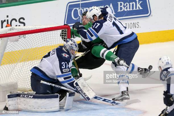 Dallas Stars Winger Devin Shore is shoved into the goal by Winnipeg Jets Center Adam Lowry during the NHL game between the Winnipeg Jets and Dallas...