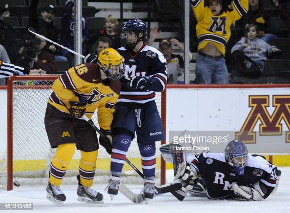 Dalton Izyk and John Rey of the Robert Morris Colonials and Nate Condon of the Minnesota Golden Gophers look on as a shot by Justin Kloos of the...