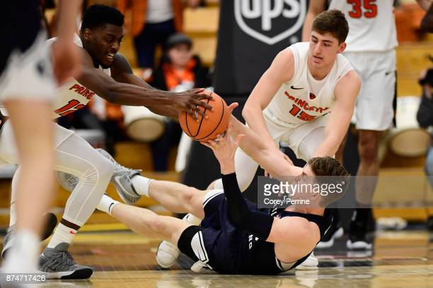 Dalton Nixon of the Brigham Young Cougars loses the ball against Myles Stephens of the Princeton Tigers and teammate Ryan Schwieger during the second...
