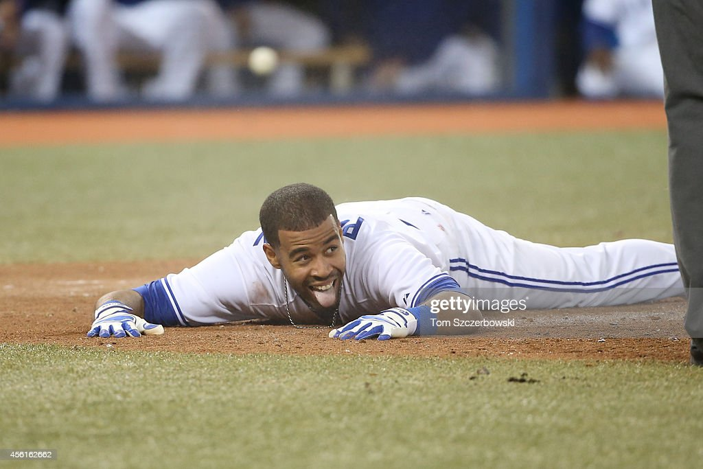 Dalton Pompey of the Toronto Blue Jays reacts after sliding into home plate to score a run in the third inning during MLB game action beating the tag...