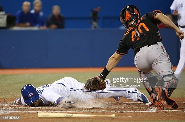 Dalton Pompey of the Toronto Blue Jays slides into home plate to score a run in the third inning during MLB game action beating the tag by Nick...