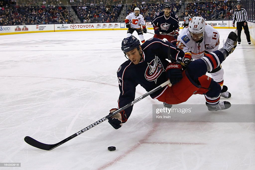 Dalton Prout #47 of the Columbus Blue Jackets looses his footing while battling for a loose puck with Jarome Iginla #12 of the Calgary Flames during the third period on March 22, 2013 at Nationwide Arena in Columbus, Ohio. Columbus defeated Calgary 5-1.