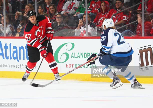 Dalton Prout of the New Jersey Devils controls the puck while being defended by Patrik Laine of the Winnipeg Jets at Prudential Center on March 28...