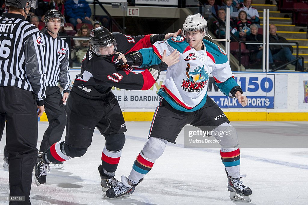 Dalton Yorke #5 of the Kelowna Rockets drops the gloves during first period with Aaron Macklin #11 of the Prince George Cougars on February 25, 2014 at Prospera Place in Kelowna, British Columbia, Canada.