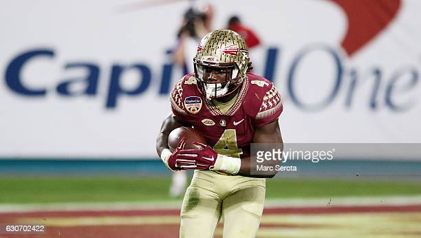 Dalvin Cook of the Florida State Seminoles carries the ball in the second half against the Michigan Wolverines during the Capitol One Orange Bowl at...
