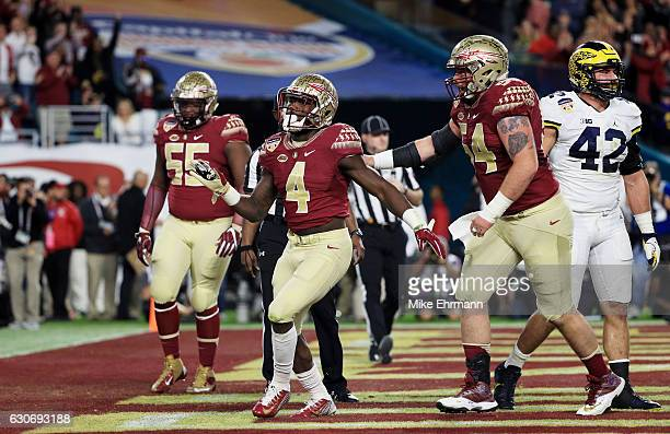 Dalvin Cook of the Florida State Seminoles celebrates his touchdown in the first quarter against the Michigan Wolverines during the Capitol One...