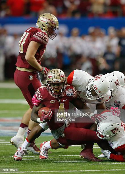 Dalvin Cook of the Florida State Seminoles is tackled by Elandon Roberts and Tyus Bowser of the Houston Cougars in the second quarter during the...