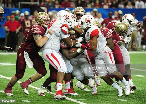 Dalvin Cook of the Florida State Seminoles is tackled by Nick Thurman Elandon Roberts and Jerard Carter of the Houston Cougars during the ChickFilA...